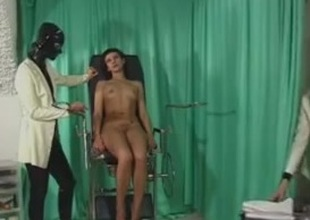Two dominas are using sex toys aloft their female attendant
